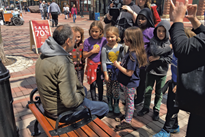 Newspaper staffers from George Leal's second grade class at the Integrated Arts Academy interviewing bystanders on Church Street after a flash mob featuring fellow students
