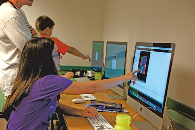 Young programmers work on digital art at Code Camp.