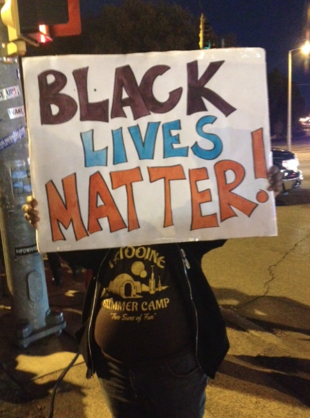 A protester near the intersection of Poplar and Highland. - LOUIS GOGGANS