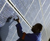 JUSTIN FOX BURKS - A Sharp employee inspects a photovoltaic module.