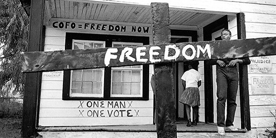 After the Ku Klux Klan burned this cross in front of a Mississippi Delta Freedom House, a civil rights worker transformed it with a painted message. Tamio Wakayama. Indianola, Mississippi, 1964