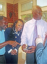 BY JACKSON BAKER - Calvin Anderson and Gale Jones Carson admire the mayor's new iPhone.