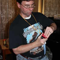 Carlin Stuart, the co-chair of MidSouthCon, prepares his Iron Man ring.
