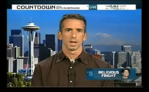 Dan Savage on MSNBC in a shirt with a collar.