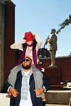 Enjoy historic tunes in style. On Darnell: his own button-down, watch, and suit jacket. Cashmere scarf by Ermenegildo Zegna, $295; from Oak Hall. Cane with brass duck head, $47.50; from Lansky at The Peabody. On Elizabeth: red fedora, $50; from Lansky 126; turtleneck by M Missoni, $395; gray wide-leg flannel trousers with leather detail by Helios & Luna, $285; purple cashmere scarf by Kinross, $235; necklace by Angel Court, $325; all from James Davis in Laurelwood. Loeffler Randall pumps, $450; from Oak Hall.