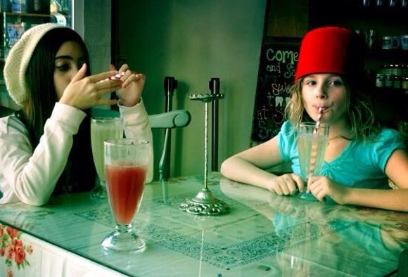 Little people enjoying floats, phosphates and funny hats at A. Schwab's soda fountain.