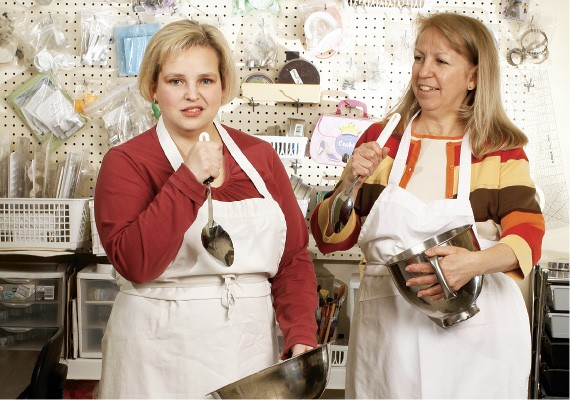 Lori Laird, left, and Pam Reed break from baking for Elvis impersonations.