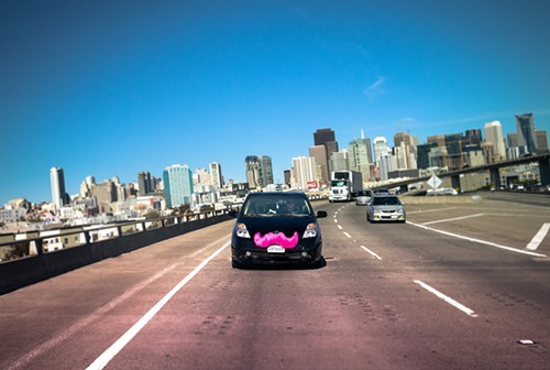Lyft cars have pink moustaches.