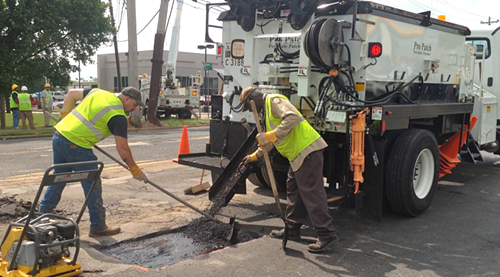 Memphis Public Works road workers show off the citys new pothole-fixing truck.