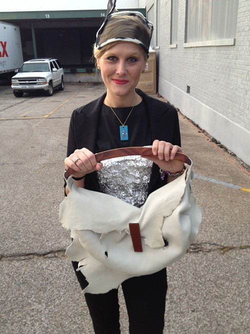 Model shows off a hat made of a screen door and a bag made of scrap leather and chair parts.