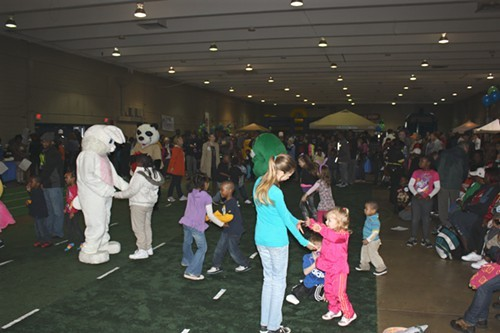 More children dancing on the makeshift lawn in the Plipkin Building. The Easter Egg Roll was moved inside due to inclement weather.