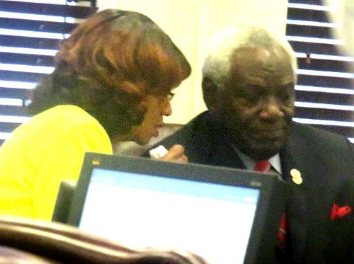 Ousted Commissioner Henri Brooks consults with Commission ally Walter Bailey on Wednesday