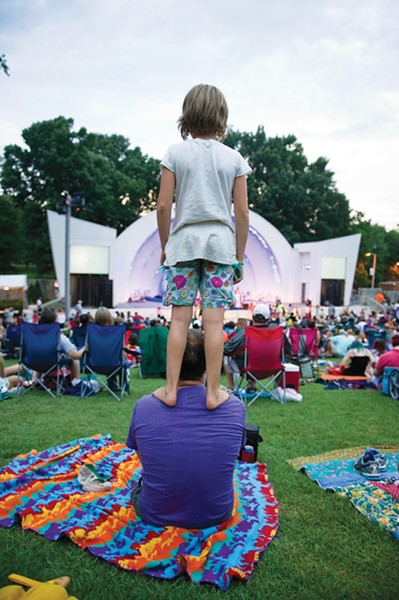 Poppy Belue, 9, stands up on her father Michael Belue for a better view as they watch Cedric Burnside Project perform during the free summer concert series at the Levitt Shell in Overton Park. - BRANDON DILL