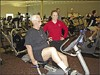 Prairie Life Fitness Center member Emory Brown (pictured on the bike) has lost 50 pounds since knee-replacement surgery. His trainer, Callie Franks, is pictured next to him.