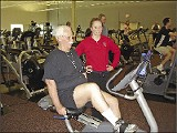 PHOTO COURTESY PRAIRIE LIFE FITNESS CENTER - Prairie Life Fitness Center member Emory Brown (pictured on the bike) has lost 50 pounds since knee-replacement surgery. His trainer, Callie Franks, is pictured next to him.