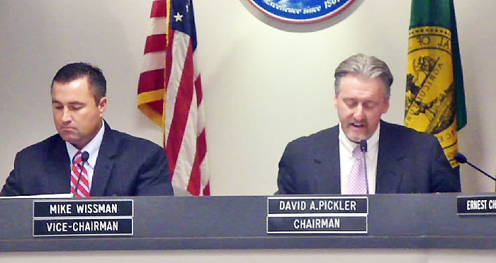 SCS chair David Pickler (right) reads Board resolution, as vice chair Mike Wissman listens. - JB