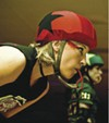 "Skaters ""Cutthroat Cutie"" and ""Your Mom"" sport game faces at a derby bout."