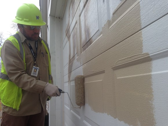 Steven Dortch of Dortch Construction paints over graffiti on an abandoned house close to MLK College Preparatory School and Frayser Achievement Elementary School. - TOBY SELLS