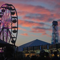 The iconic Bonnaroo ferris wheel and clock tower against a Saturday night sunset.