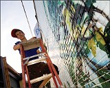 BY CHRISTOPHER PARKS - U of M graphic design student Brandon Marshall works on a mural on Highland.