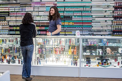 Thomas Ian Eubanks mans the counter at Create A Cig, where more than 100 flavors of e-liquid line the wall.