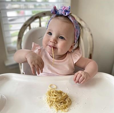 Lottie Dorroh eating restaurant-style pasta in her high chair - COURTESY OF JUSTIN DORROH