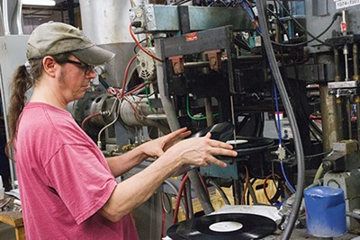 A worker at Memphis Record Pressing inspects a record before sending it to the listening station - JOSH MILLER
