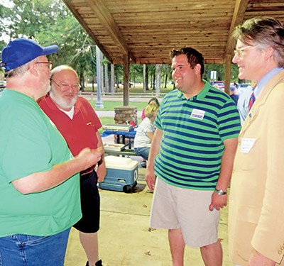 The races had their share of underdogs. Here candidates - Charley Burch (right), running for Super District 9, Position 1, - and Zachary Ferguson (second from right), candidate for the - Super District 9, Position 3 seat,  make their pitches to picnicking Democrats Steve Steffens (left) and Joe Weinberg. - JACKSON BAKER