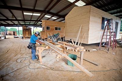 A carpenter cuts trim for exterior window casings - JUSTIN FOX BURKS