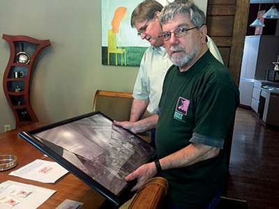 Redneck BBQ Express founding members Pete Gross and Woody Coleman look over memorabilia. - TOBY SELLS
