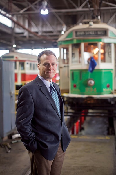 Ron Garrison, CEO of MATA, stands in front of a trolley.