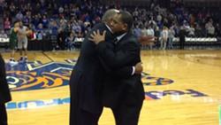Father embraces son.