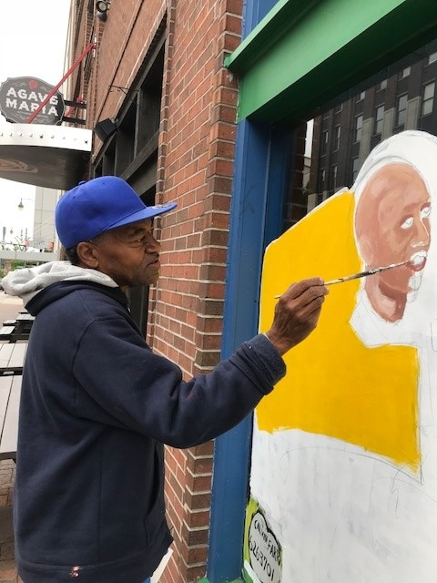 Farrar paints Penny for a mural on Parking Can Be Fun