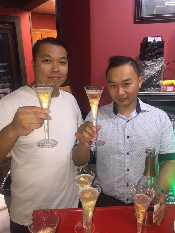 Jimmy Sinh and his brother, David Sinh, toast during the grand re-opening of Sushi Jimmi Asian fusion restaurant. - MICHAEL DONAHUE