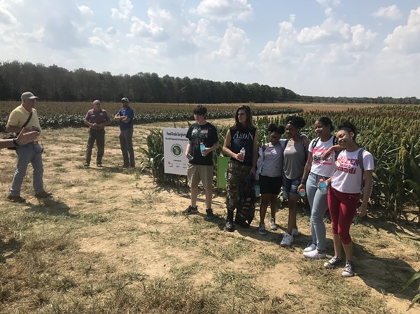 A group of Crosstown High School students pose for a photo before a stand of sorghum at the Future of Ag Field Day at Agricenter. - TOBY SELLS