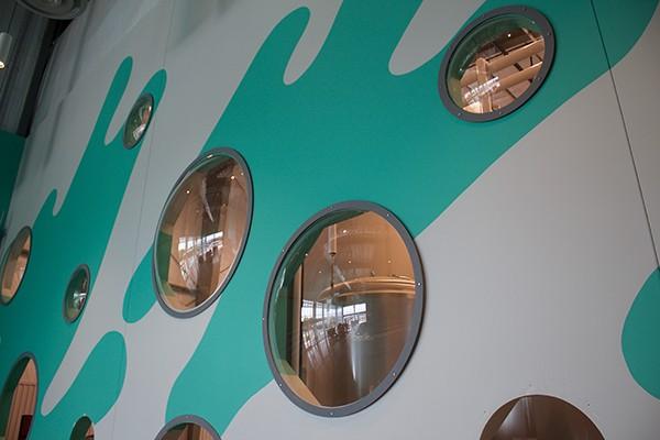 Les fenêtres à bulles amplifient une fresque de taverne et offrent une vue dégagée sur la nouvelle brasserie brillante. - WISEACRE BREWING CO.