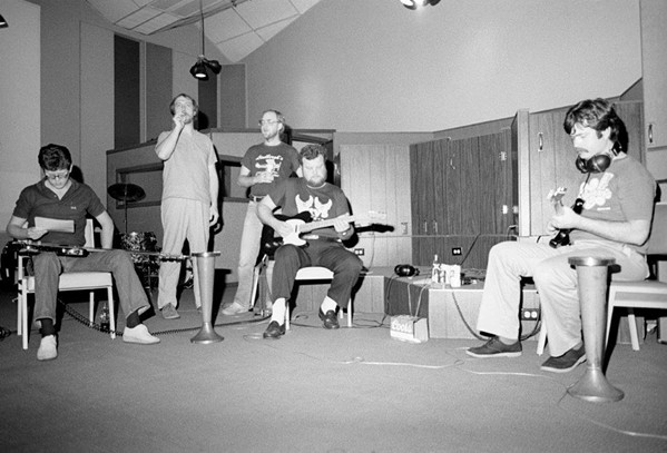 Jim Blake smokes a joint while musicians prepare for a recording session, 1970s. - PAT RAINER