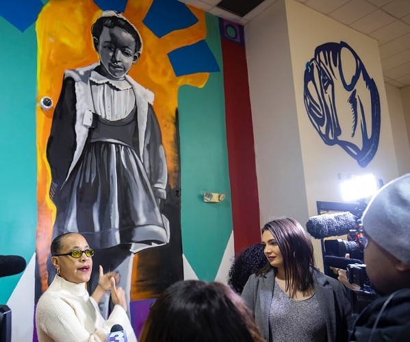 Dwania Kyles, one of three students who integrated Bruce Elementary in 1961, stands in front of Jamond Bullock's mural. - JAMOND BULLOCK
