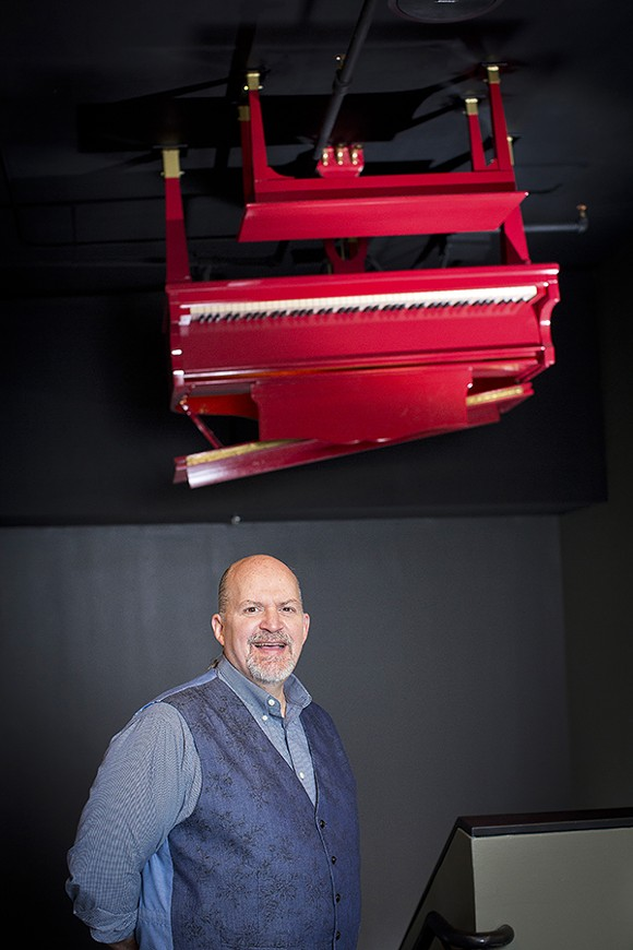 John Doyle, executive director of the Memphis Music Hall of Fame, stands art the top of the stairs where a glowing piano stands in for a traditional light fixture. - JUSTIN FOX BURKS