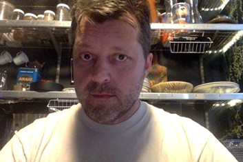 Update: I'm in my kitchen writing a review of Krapp's Last Tape. And I need a shave. Also, even though you can't see it, there's an entire bunch of overripe bananas hanging behind my head. - ME