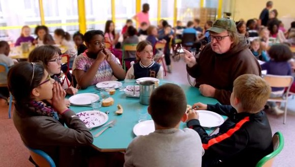 Moore talks with children around a French school lunch table.