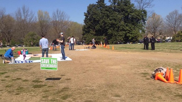 "Protesters sit and play in the Greensward's ""cone zone."" - FACEBOOK"