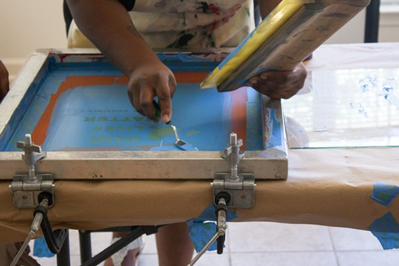 Apprentice Ca'Terrya Hilson works on screen printing during an exhibition hosted by the Klondike/Smokey City Community Development Center. - ELLE PERRY