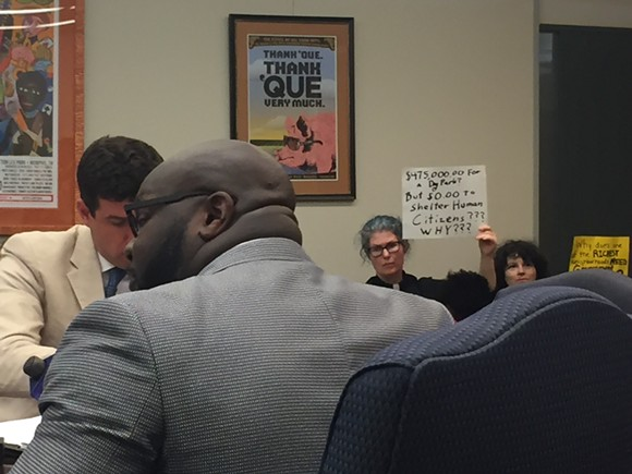A protestor holds a up a sign as council member Berlin Boyd explains the Mud Island Dog Park project. - TOB SELLS