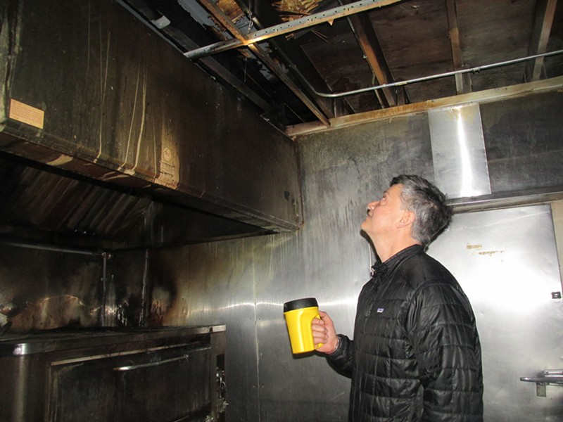 Michael Bomarito examines fire damage in the prep area of Pete and Sam's restaurant. - MICHAEL DONAHUE