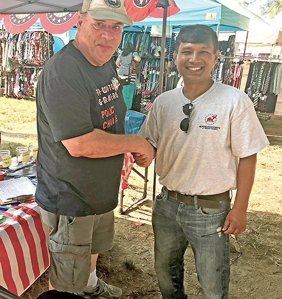 Fellow sufferers: David Cambron (l), president of the Germantown Democratic Club, and Naser Fazlullah, outreach chairman of the Shelby County Republican Party, endured 90-degree temperatures to represent their respective parties at last weekend's annual Germantown Festival. Their handshake symbolized a common faith in the democratic process. - JACKSON BAKER
