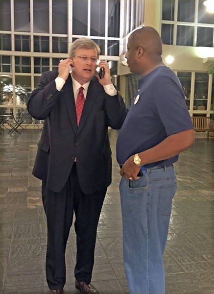Mayor Strickland receives congratulations by phone from runner-up Herenton at Botanic Gardens, as aide Ken Moody looks on.