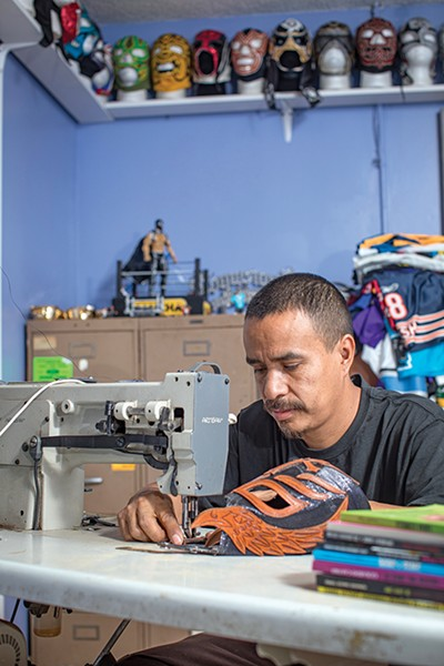 Enrique Reyes is hard at work on a colorful lucha libre mask at his business, Reyes Customs.