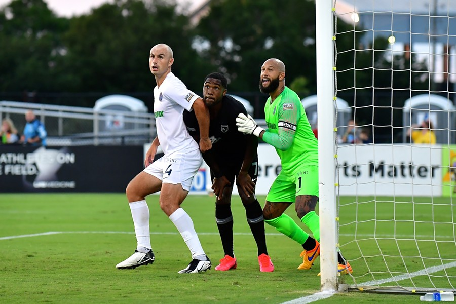 Centerback Liam Doyle (left) and Howard tussle with Birmingham forward Brian Wright. - PHOTO BY ERIC GLEMSER