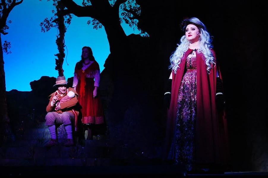 Renee Davis Brame (right) as The Witch in Into the Woods at Theatre Memphis on the Lohrey Stage, March 11 - April 3, 2016. Lee Gilliland (left) as the  Baker holds his child and the Baker's Wife, Lynden Lewis, looks on from the shadows. - JCK YATES